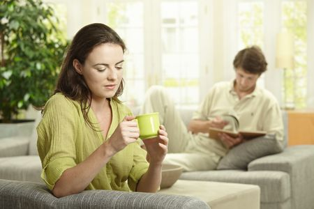 Young  couple resting at home, reading book and drinking coffee. Selective focus on women. photo
