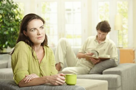 sipping: Young  couple resting at home, reading book and drinking coffee. Selective focus on women.