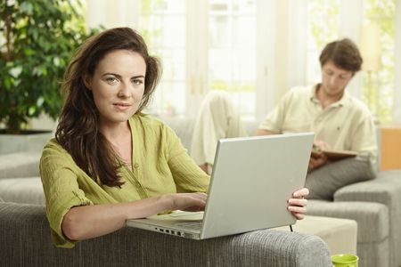 Couple at home. Woman using laptop computer, man reading book in background. photo