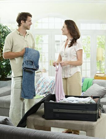 Happy couple packing clothes into suitcase, preparing for vacation. photo