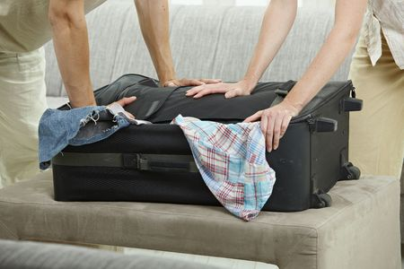 luggage travel: Hands trying to close full suitcase, pressing down.