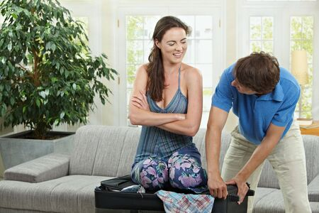 Happy couple packing for holiday, woman trying to close suitcase full with clothes. photo