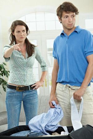 Unhappy couple fighting. Woman pointing out, man packing his clothes. photo