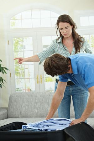 Unhappy couple fighting. Woman pointing out, man packing his clothes. Stock Photo - 5754786
