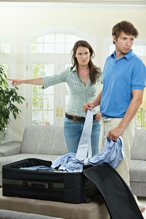yelling: Unhappy couple fighting. Angry woman pointing out, man packing his clothes into suitcase. Stock Photo