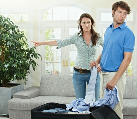 Unhappy couple breaking. Angry woman pointing out, man packing his clothes into suitcase. photo