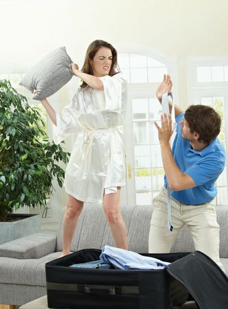 Unhappy couple fighting. Woman hitting man who is  packing his clothes with a pillow. Stock Photo - 5754778