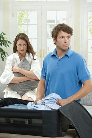 Unhappy couple breaking. Man packing his clothes into suitcase, sad woman hugging pillow in the background. Selective focus on woman. photo