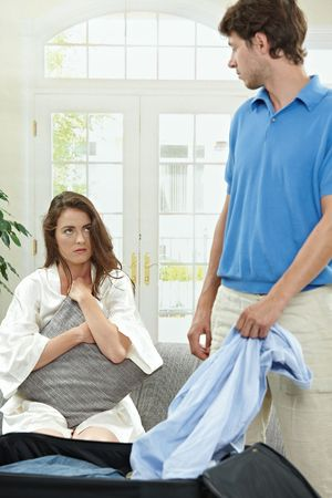Unhappy couple breaking. Man packing his clothes into suitcase, crying woman hugging pillow in the background. Selective focus on woman. photo