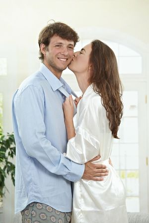 Happy couple embracing and kissing at home in the morning. photo
