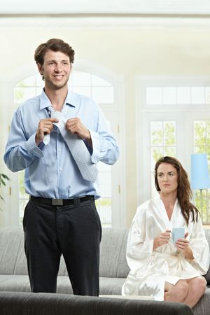 Couple in the morning. Man dressing up, woman drinking tea. photo