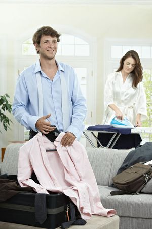 Young businessman preparing for business trip. Woman ironing in the background. photo