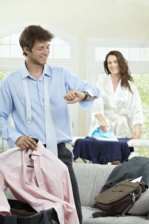 Young businessman going to business trip, looking at his watch. Woman ironing in the background. photo