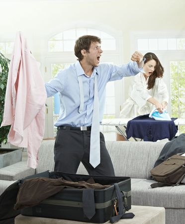 panicked: Panicked couple packing for business trip, they are late. Stock Photo