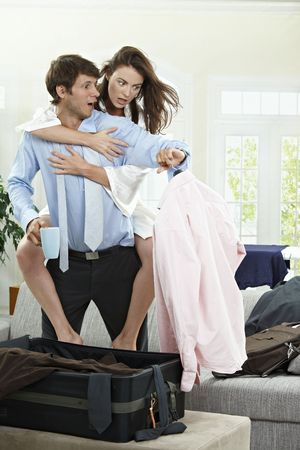 panicked: Panicked couple packing for business trip in the morning, they are late. Stock Photo