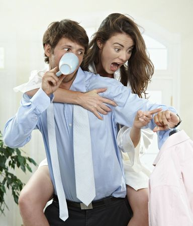 Panicked couple packing in the morning at home, they are late for work. photo
