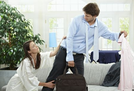 personas discutiendo: Romper pareja infeliz. La mujer tratando de contener el hombre, leawing con la maleta y la ropa en la mano.