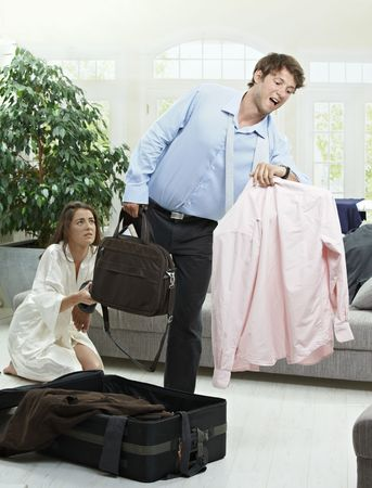 Young businessman leaving for business trip, woman holding him back. photo