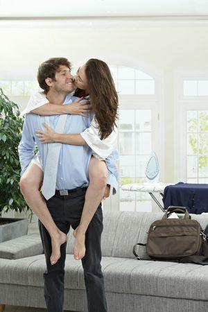 together with long tie: Happy joven empresario sosteniendo su girfriend, besos.