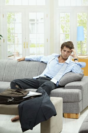 single rooms: Tired businessman resting on couch at home after long day of work.