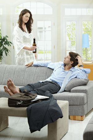 Tired businessman resting on couch at home after long day of work. Woman giving him bottle of beer. Stock Photo - 5754780