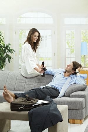 Tired businessman resting on couch at home after long day of work. Woman giving him bottle of beer. photo