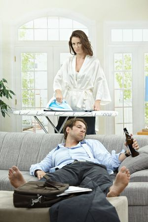 wives: Tired businessman resting on couch with beer in hand. Angry wife ironing in the background. Stock Photo
