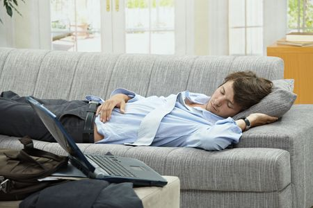 look after: Tired businessman resting on couch at home after long day of work.