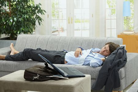 Tired businessman sleeping on couch at home after long day of work. photo