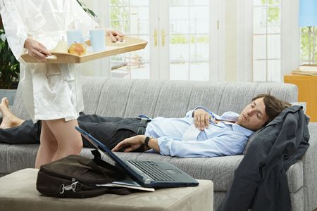 Tired businessman sleeping on couch at home in the morning, his wife bringing breakfast on tray. photo