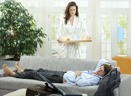 Tired businessman resting on couch at home in the morning, his wife brining breakfast on tray. photo