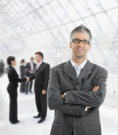 gratified: Portrait of happy businessman standing with hands crossed in office lobby, smiling. Stock Photo