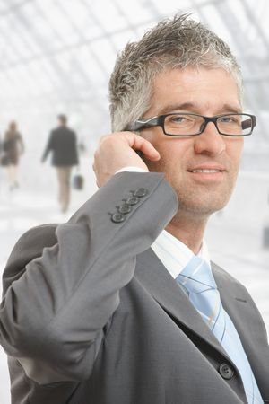 gratified: Closeup portrait of businessman talking on mobile in office lobby. Stock Photo
