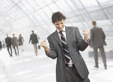 Happy young businessman celebrating business success with fists clenched, smiling.  Isolated on white. photo