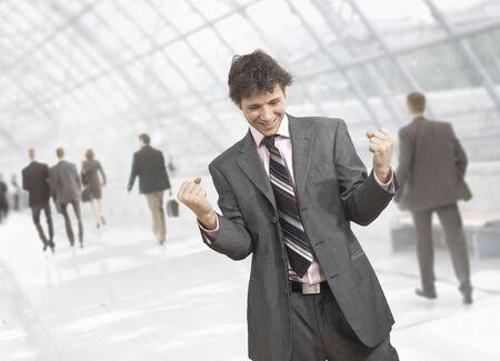 Happy giovane uomo d'affari che celebra il successo del business con i pugni chiusi, sorridendo. Isolati su bianco.