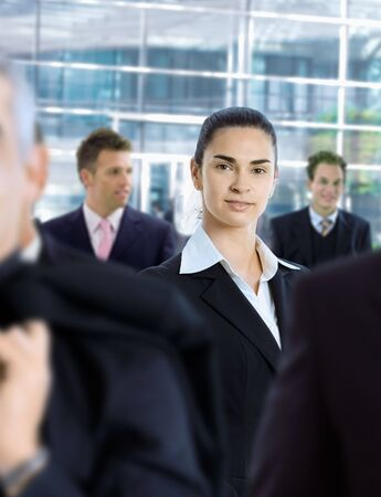 officetower: Young businesswoman standing amongt other businesspeople,in front of office building. Stock Photo