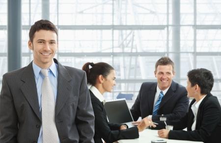 n�gocier: Happy businessman debout � l'avant, les gens d'affaires parlent au bureau dans le fond.