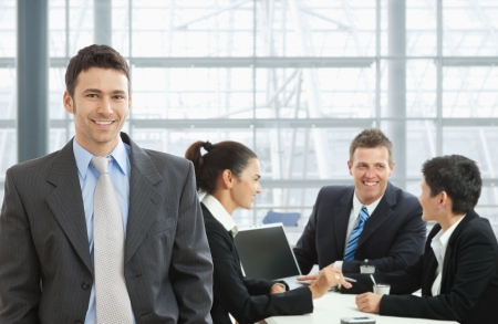 Happy businessman standing in front, businesspeople talking at desk in the background. photo