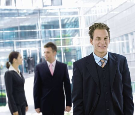 Businessman leaving office building aong other businesspeople in the background. photo