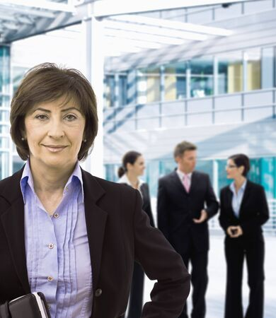 Portrait of senior businesswoman standing in corporate office lobby, smiling. photo