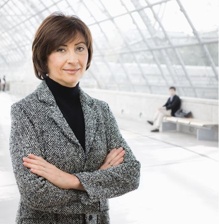 undoubting: Portrait of senior businesswoman wearing grey suit, posing arms crossed in office lobby.