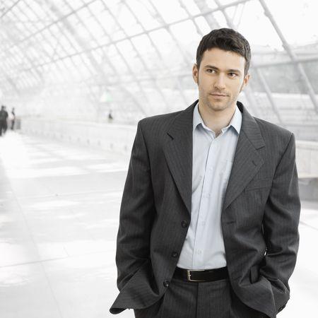after to work: Retrato de hombre de negocios de pie en el vest�bulo de la oficina cansado despu�s del trabajo, en camisa de cuello abierto sin corbata.