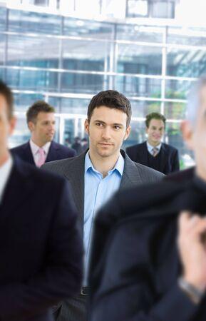 Casul businessman walking in crowd in office lounge. Stock Photo - 5758850