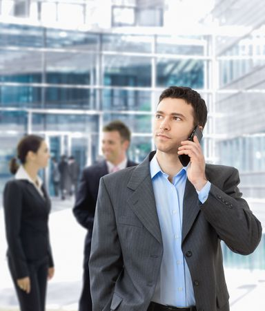 Serious businessman talking on mobile standing in office hallway. Stock Photo - 5758704