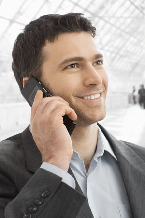 Closeup portrait of happy businessman talking on mobile in office lobby. photo