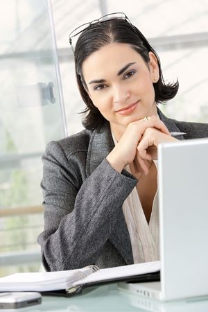 Young businesswoman thinking leaning on hands, sitting at office desk. photo