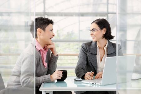 Happy young businesswomen working together at desk in modern office, looking at each other, laughing. photo