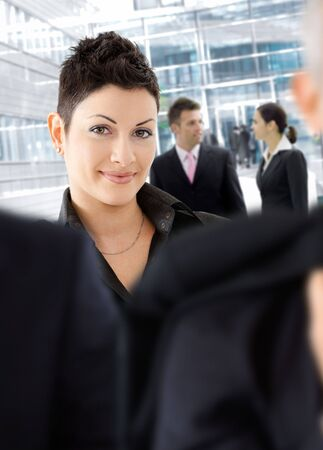 Young businesswoman standing among other businesspeople otside of office building. photo