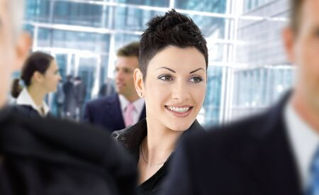 Happy businesswoman standing among other businesspeople otside of office building, smiling. photo