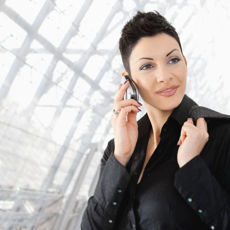 Closeup portrait of young businesswoman talking on mobile phone on office lobby. photo